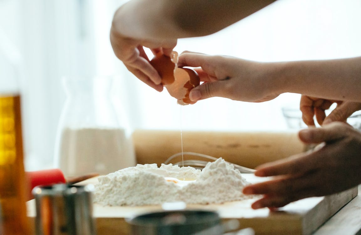 Crop young lady breaking eggs in flour for dough