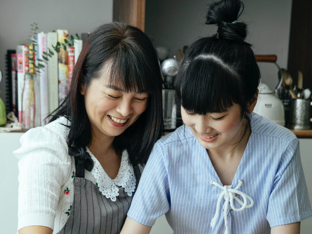 Asian mother standing with daughter on kitchen