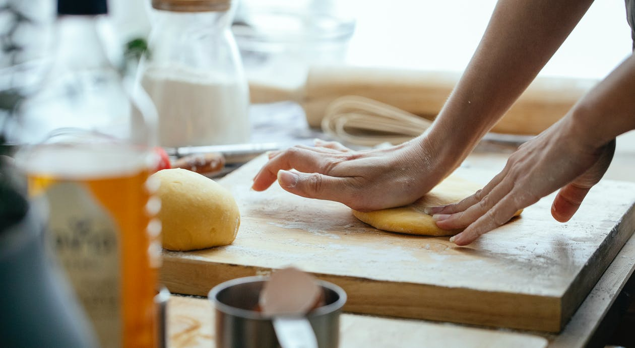Female hands kneading fresh dough on wooden chopping board with flour in kitchen