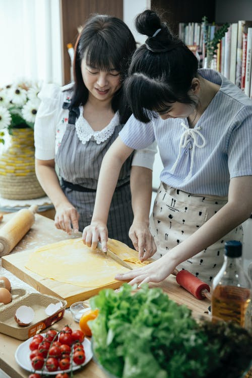 High angle of Asian women in aprons cutting dough for pasta on table with vegetables eggs and cooking ingredients