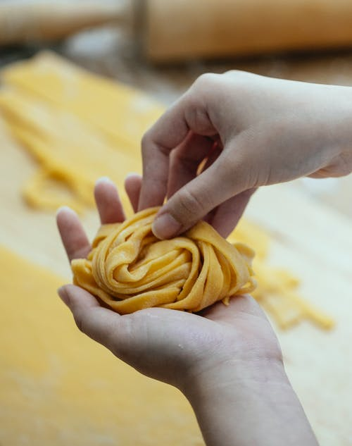Female hands with rolling long strips of homemade raw noodles for cooking Asian food