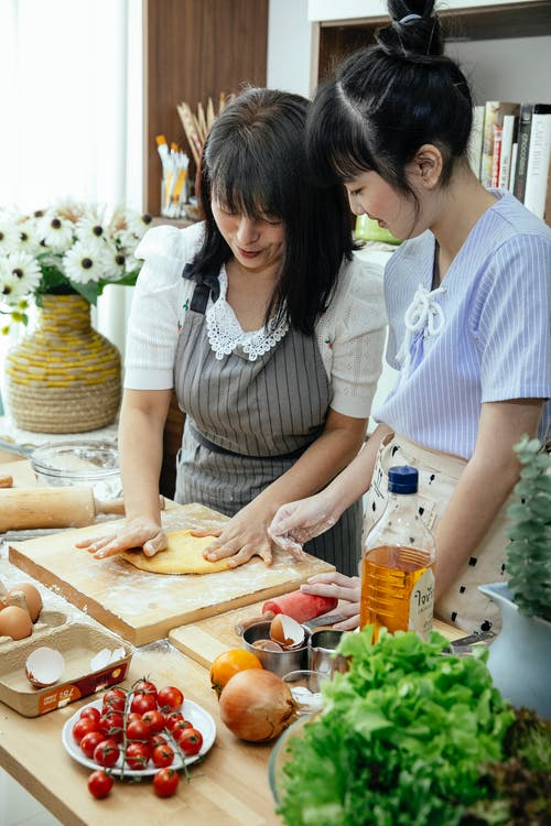 Asian women making dough for oriental dish