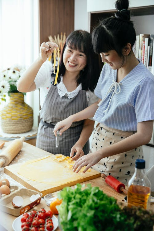 Mother and daughter cooking together homemade noodles