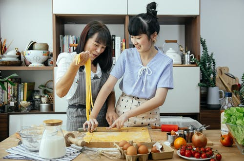 Smiling women making noodles in kitchen