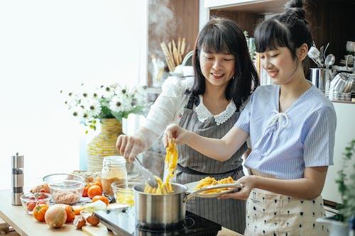Happy Asian women cooking oriental noodles in kitchen