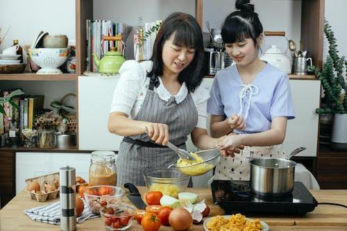 Happy women making pasta in light kitchen