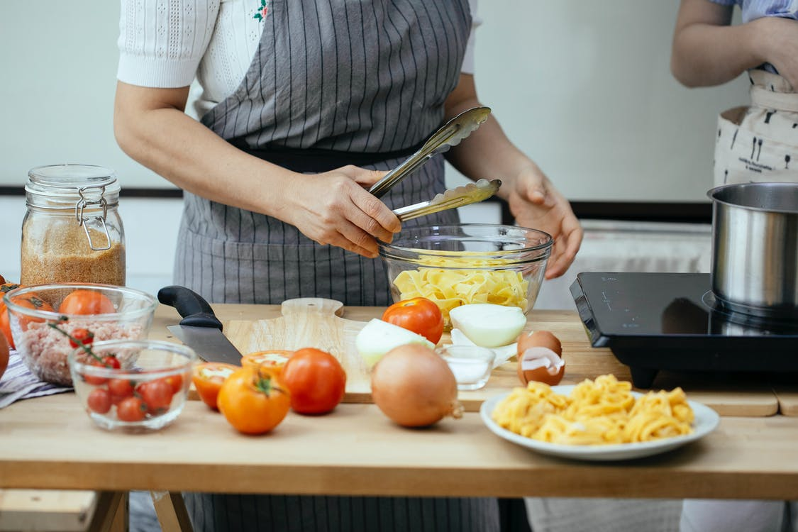 Faceless women in aprons cooking delicious pasta with fresh tomatoes standing at counter in modern kitchen