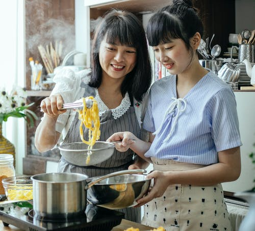 Smiling Asian mother and daughter preparing delicious pasta