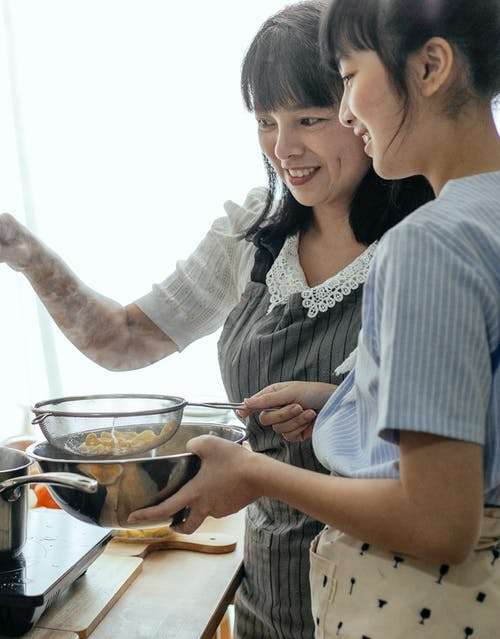 Smiling women cooking pasta together