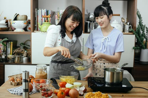 Laughing Asian mother and daughter preparing pasta in kitchen