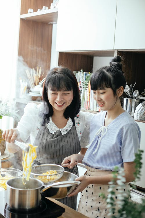 Young Asian women cooking together in kitchen