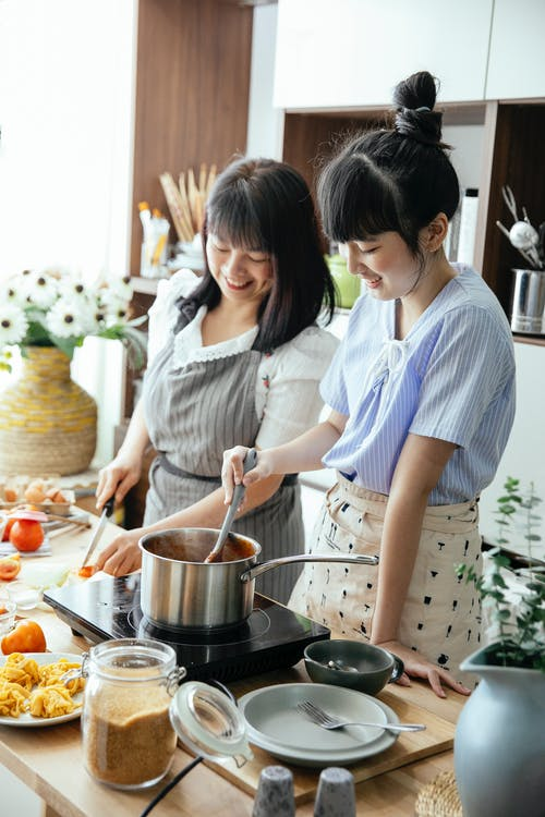 Cheerful Asian woman with young daughter smiling while cutting veggies and stirring sauce during lunch preparation together in kitchen
