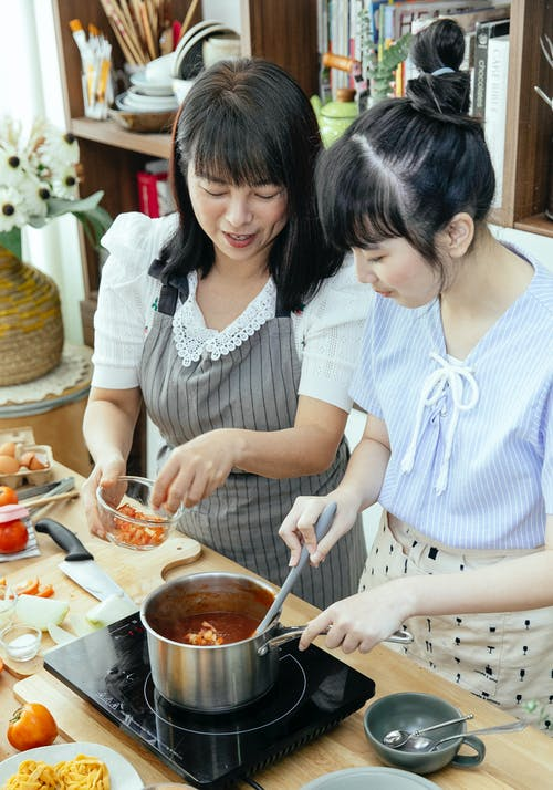 Ethnic women in aprons standing near table and cooking and stirring pasta at home