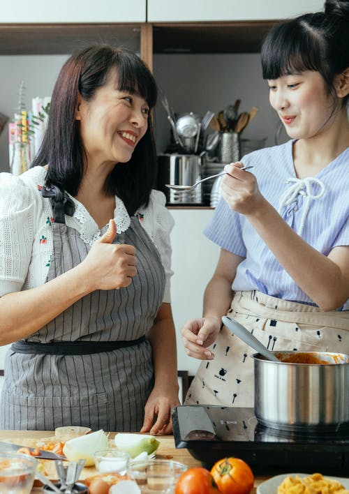 Happy Asian mother and daughter cooking in kitchen