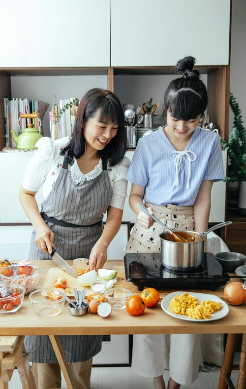 Positive Asian mother cutting vegetables while standing at table near daughter stirring food in pan while cooking together in kitchen