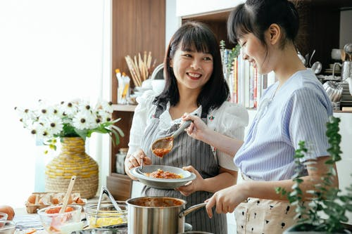 Asian women cooking together in kitchen