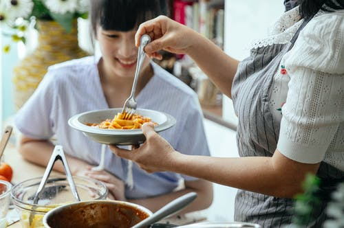Ethnic women serving cooked pasta for meal