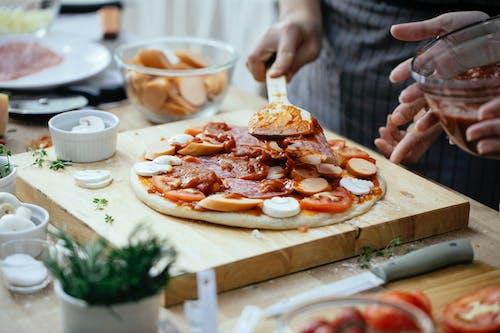Crop people adding sauce on pizza