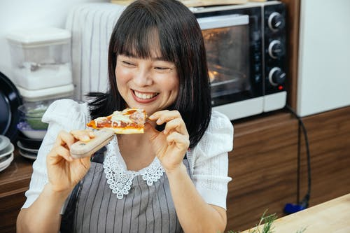 Happy Asian woman enjoying eating slice of cheesy pizza sitting at table in kitchen