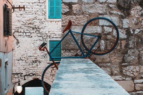 Blue Bicycle on Top of Concrete Fence