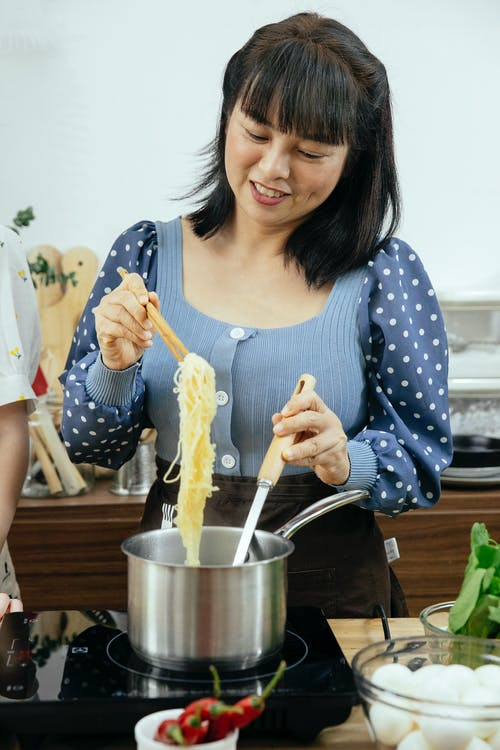Woman cooking noodles in kitchen