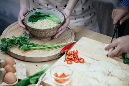 Unrecognizable woman with bowl cooked noodles and leek and unrecognizable person cutting egg on chopping board in kitchen