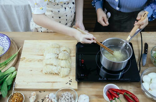Crop anonymous housewives in aprons boiling noodles on tabletop stove near fresh ingredients in modern kitchen