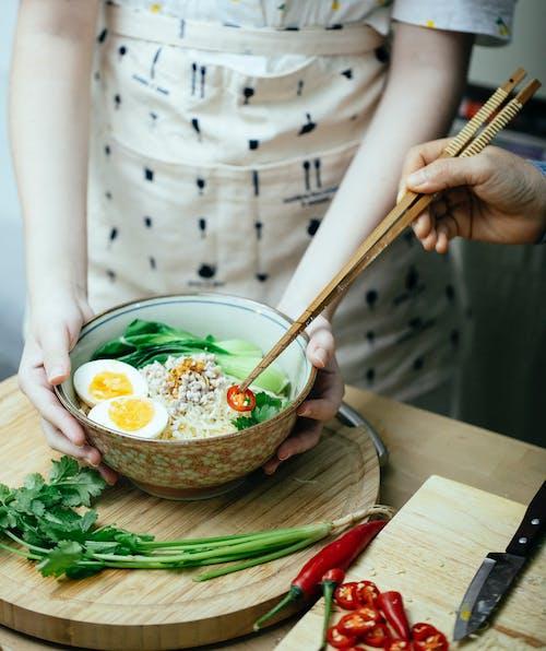 Crop unrecognizable women garnishing Asian soup with cut pepper