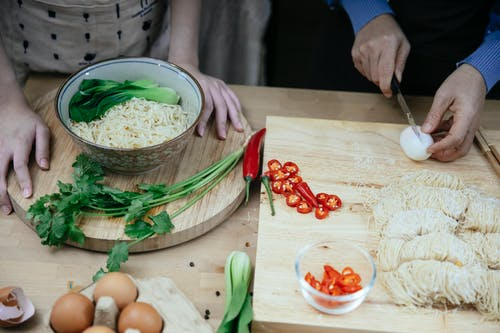 From above anonymous females cutting boiled eggs on wooden cutting board while cooking traditional Asian noodle soup in kitchen