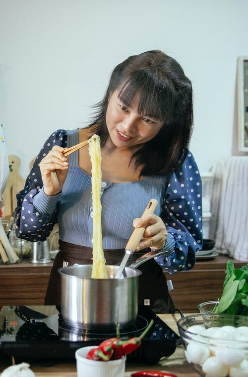 Happy Asian woman boiling noodles in modern kitchen