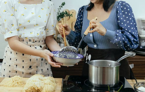 Crop anonymous housewives in stylish wear putting homemade boiled noodles into bowl while cooking together in modern kitchen