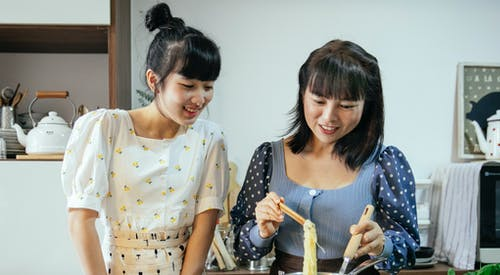 Cheerful Asian women boiling noodles in kitchen