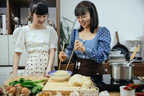 Smiling content Asian females wearing stylish clothes and aprons with chopsticks cooking yummy noodles on kitchen counter