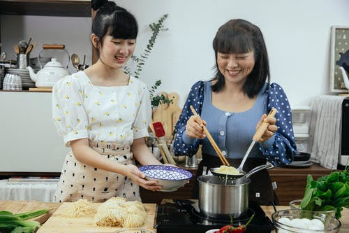 Happy Asian females in stylish clothes and aprons putting tasty boiled noodles into bowl while cooking traditional Asian dishes together in modern kitchen
