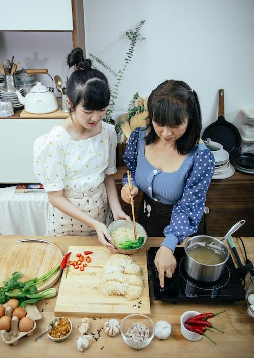 Positive Asian women adding pak choi cabbage into noodle soup