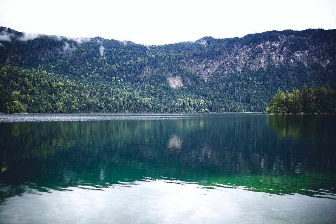Body of Water With Green Mountain at Distance
