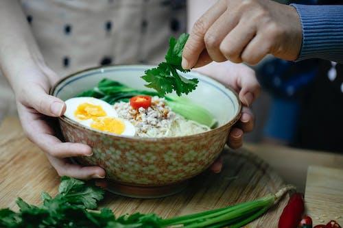 Crop unrecognizable women decorating Asian noodle soup with parsley