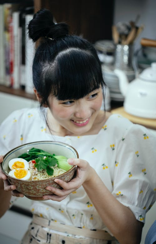 Happy smiling Asian female in stylish wear demonstrating freshly cooked Asian noodles soup in bowl and looking away contentedly