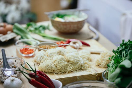 Composition of uncooked noodles and fresh vegetables on kitchen counter