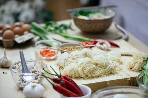 Composition of uncooked noodles on wooden board near fresh various vegetables and eggs arranged on table in kitchen before cooking Asian noodles soup