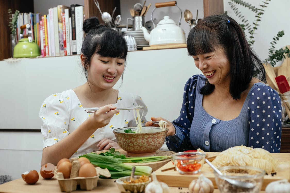 Joyful Asian women eating traditional noodles soup together