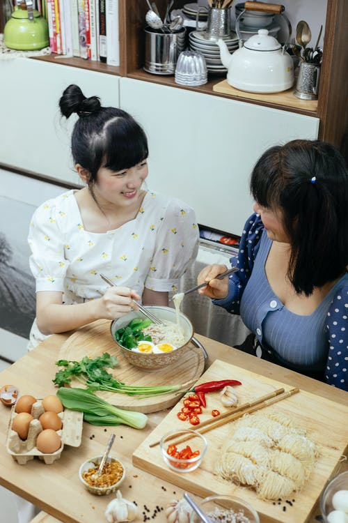 Cheerful Asian women eating tasty ramen soup and chatting