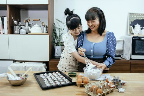 Happy Asian mother and daughter cuddling while preparing meringues in kitchen