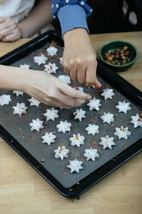 High angle of crop faceless ladies decorating freshly baked meringue cookies with flakes while preparing pastry for Christmas holidays