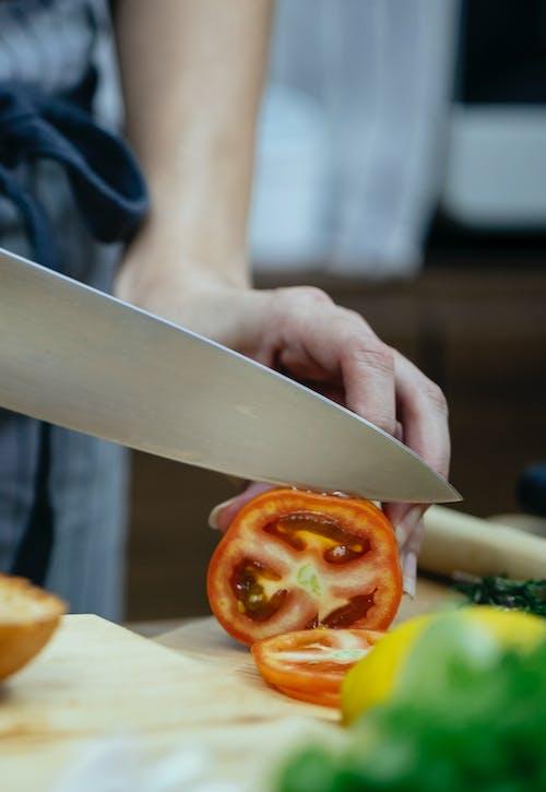 Crop woman cutting tomato on table
