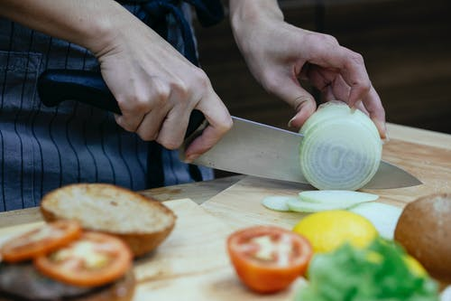 Unrecognizable female cook slicing onion on cutting board at table with blurred tomatoes and toasted buns in kitchen during cooking process