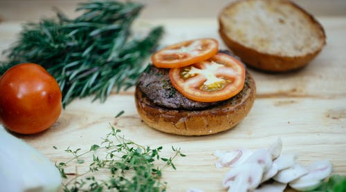 Toasted buns with cutlet and tomatoes placed on wooden table with greens and mushroom in kitchen while preparing tasty burger