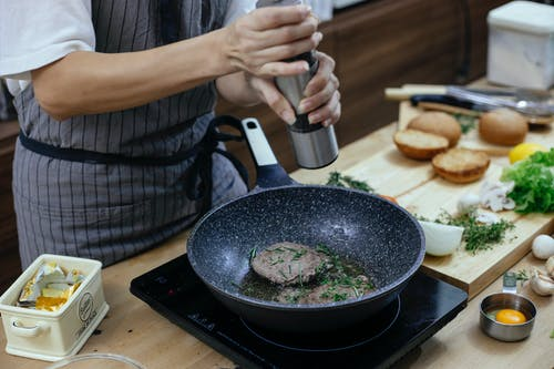 Unrecognizable female cook wearing apron adding seasoning on cutlets while preparing delicious burger at table with stove in kitchen