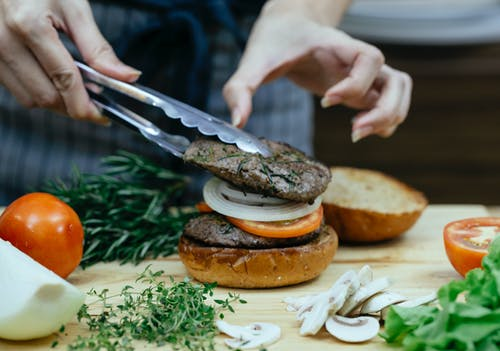Unrecognizable female cook using tongs to put juicy meat on bun with onion and slice of tomato while making burger against blurred background