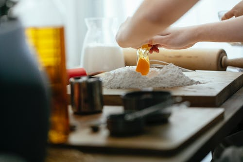 Unrecognizable cook breaking egg into pile of flour on wooden board while preparing dough at table in kitchen against blurred background